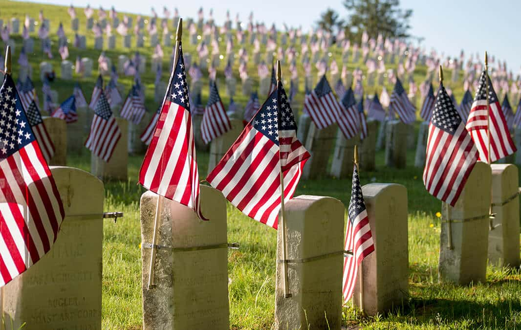 Small American flags and headstones at National cemetary